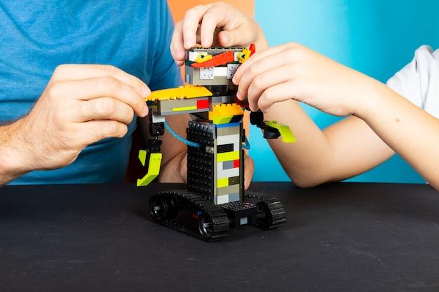 Um homem e um menino se reúnem a partir de um construtor de um robô. mãos masculinas e infantis coletam lego Foto Premium