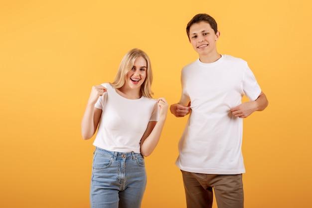 Um homem e uma mulher em uma camiseta branca são mostrados com os dedos nas camisas em um fundo laranja Foto Premium