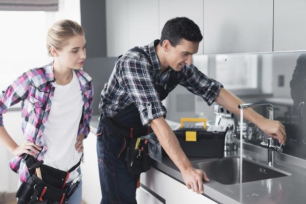 Um homem e uma mulher encanador reparar um torneira da cozinha. Foto Premium