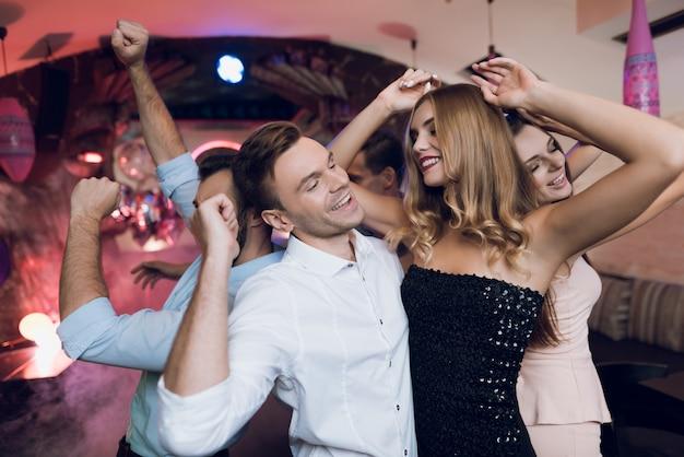 Um homem e uma mulher estão dançando em primeiro plano. Foto Premium