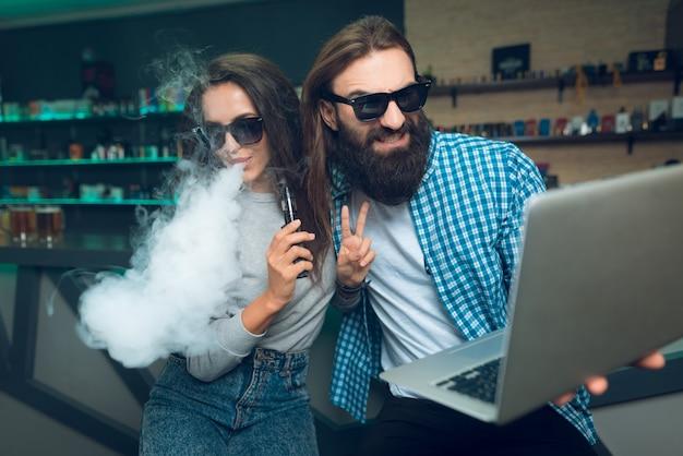 Um homem e uma mulher estão sentados com um vaporizador e laptop. Foto Premium