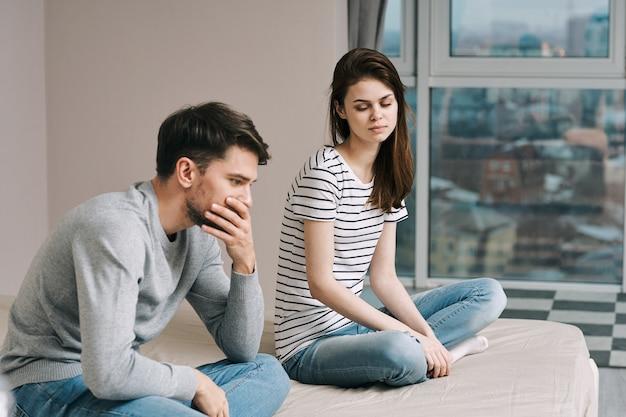 Um homem e uma mulher estão sentados na cama e conversando sobre um relacionamento, uma verdadeira briga Foto Premium