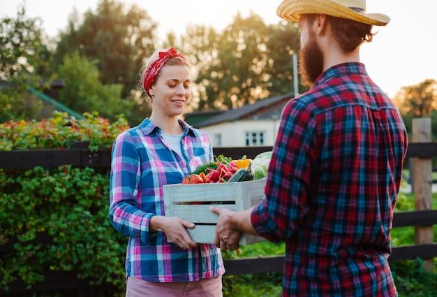 Um homem e uma mulher segurando uma caixa com uma colheita de legumes da fazenda Foto Premium
