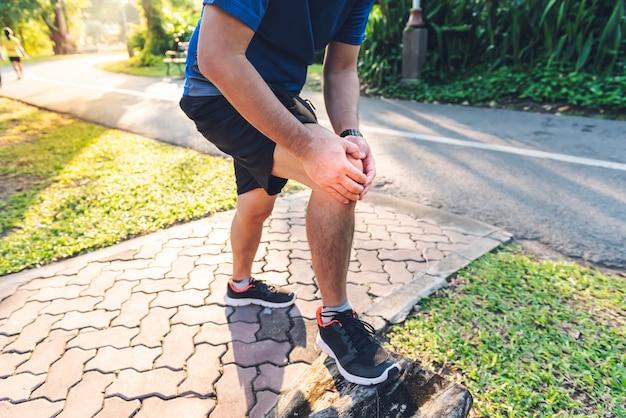 Um homem ele está atualmente tendo uma lesão no joelho durante seu exercício correndo no parque Foto Premium