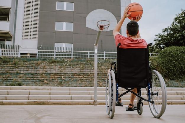 Um homem em cadeira de rodas joga basquete Foto Premium