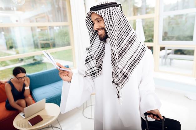 Um homem em roupas árabes está segurando uma mala. Foto Premium