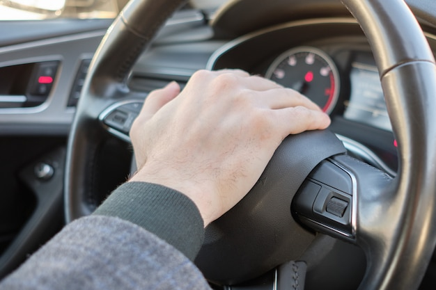 Um homem em um carro moderno. a mão pressiona o sinal sonoro e emite um sinal. Foto Premium