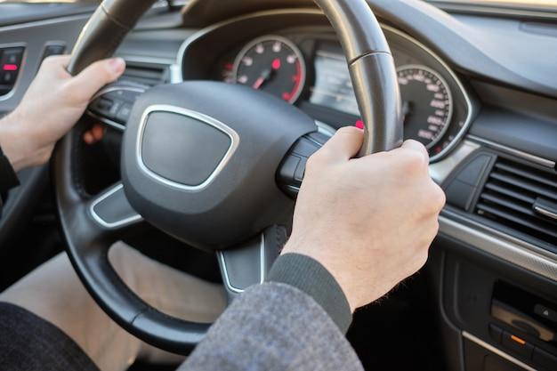 Um homem em um carro moderno. mãos segurando o volante no local correto. Foto Premium