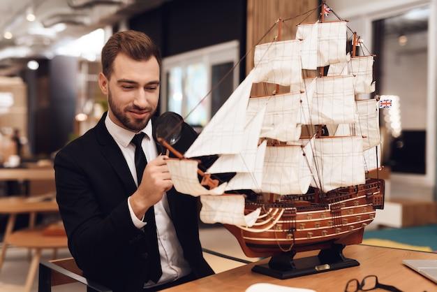 Um homem em um terno de negócio está sentado em uma mesa com um veleiro. Foto Premium