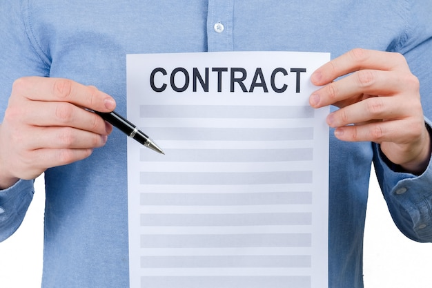 Um homem em uma camisa azul está guardando uma folha com um contrato e uma pena em um fundo branco. Foto Premium
