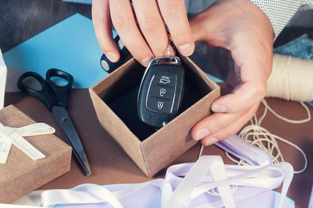 Um homem em uma camisa leve está preparando uma caixa de presente para o feriado. tonificação o carro como presente. chaves do carro na caixa de presente. Foto Premium