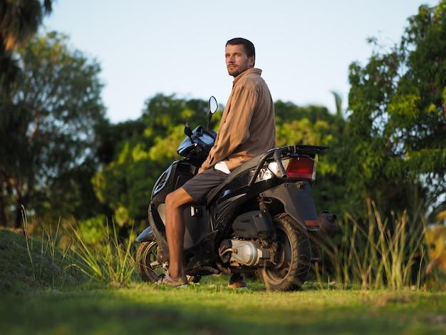 Um homem em uma scooter está sentado assistindo o pôr do sol. ambiente tropical. viajando em um ciclomotor. Foto Premium