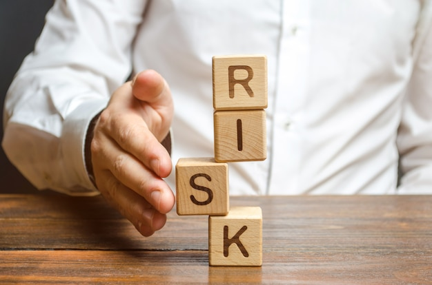 Um homem endireita um segmento em uma torre instável de cubos rotulados como risco. gerenciamento de riscos Foto Premium