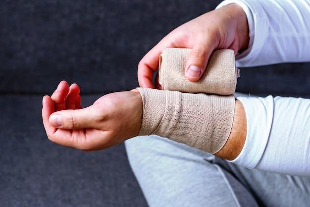 Um homem enfaixa a mão com uma bandagem esportiva. lesões e distensões no esporte. Foto Premium