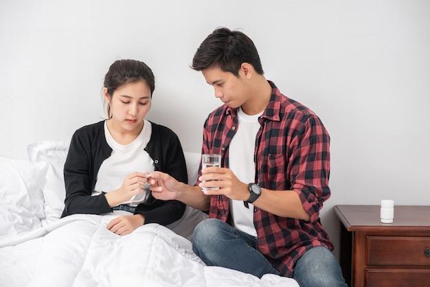 Um homem entregou remédio a uma mulher doente na cama. Foto gratuita