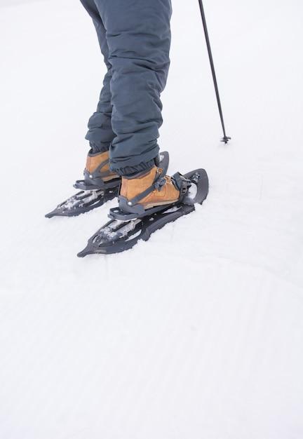 Um homem esportivo calçando suas raquetes de neve para iniciar uma excursão nas montanhas nevadas. Foto Premium