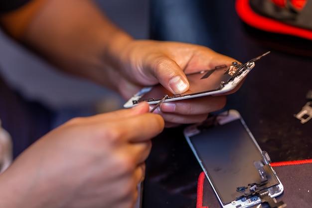 Um homem está consertando um telefone celular Foto Premium