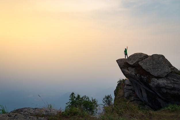 Um homem está em um penhasco íngreme com o fundo do céu da manhã. Foto Premium