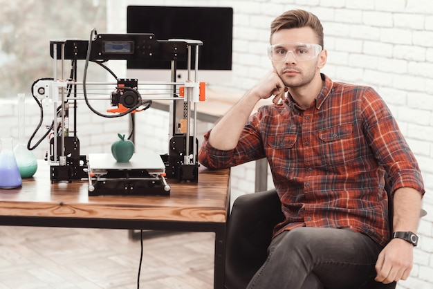 Um homem está posando perto da impressora 3d. Foto Premium