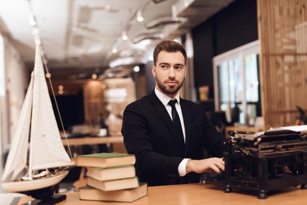 Um homem está sentado em uma mesa com uma velha máquina de escrever. Foto Premium