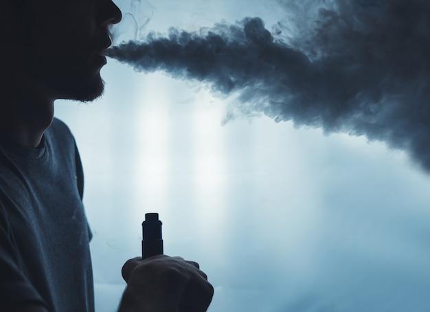 Um homem farpado nas nuvens do vapor do close up eletrônico do cigarro. vaping homem Foto Premium