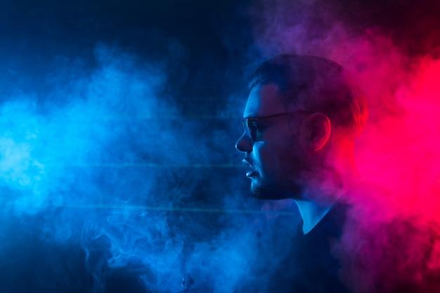 Um homem fuma um cigarro e solta fumaça em uma boate. Foto Premium