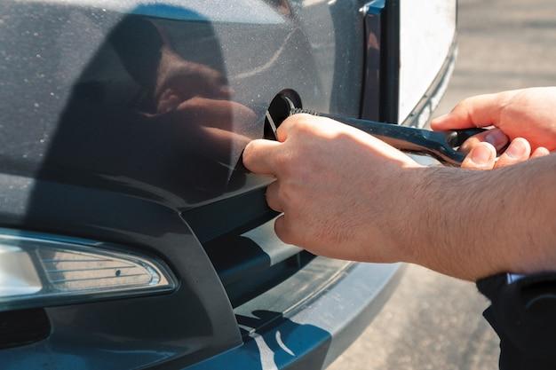 Um homem gira um gancho para rebocar na frente de um carro. avaria do carro e reboque. Foto Premium