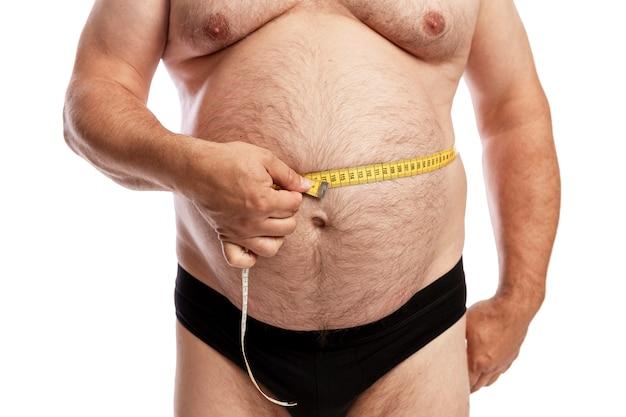 Um homem gordo de short mede o volume do abdômen. isolado. fechar-se. Foto Premium