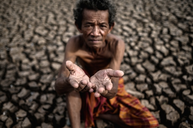Um homem idoso estava sentado pedindo chuva na estação seca, aquecimento global Foto gratuita