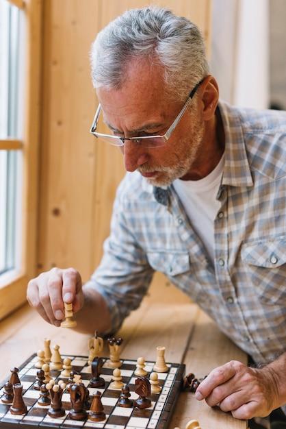 Um, homem idoso, óculos desgastando, xadrez jogando, ligado, peitoril janela Foto gratuita