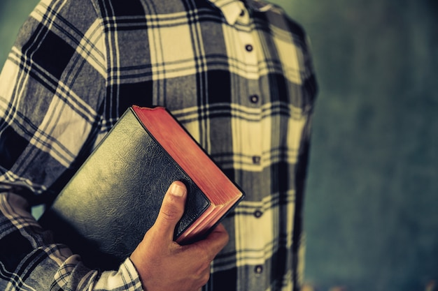 Um, homem jovem, segurando, um, bíblia, em, seu, mãos Foto gratuita