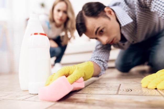Um homem limpando o chão no apartamento de uma mulher. Foto Premium
