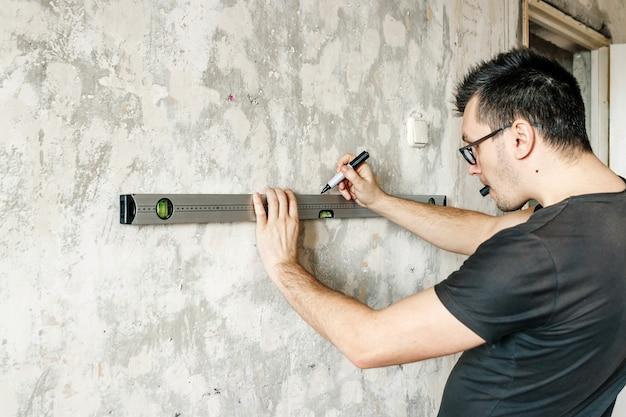 Um homem mede na parede com uma régua Foto Premium