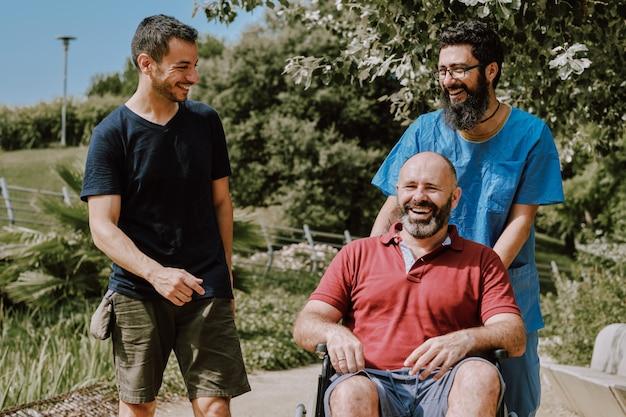 Um homem na cadeira de rodas com seu assistente e um amigo Foto Premium
