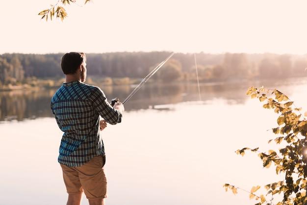 Um homem na natureza com uma pesca da vara de pesca. Foto Premium