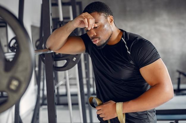 Um homem negro bonito está envolvido em uma academia Foto gratuita