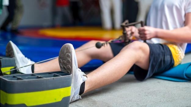 Um homem no chão da academia fazendo um exercício com um simulador Foto gratuita