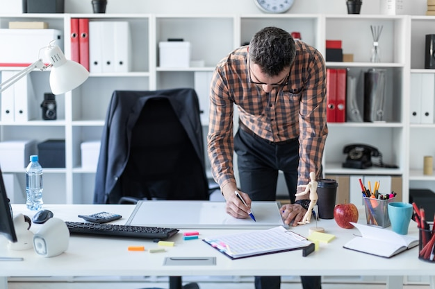 Um homem no escritório está de pé perto da mesa e desenha um marcador no quadro magnético Foto Premium