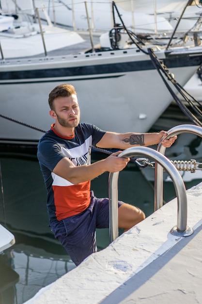 Um homem no porto preparando o iate para a viagem Foto gratuita