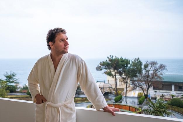 Um homem pensativo em um roupão branco está de pé na varanda com uma bela vista do mar Foto Premium