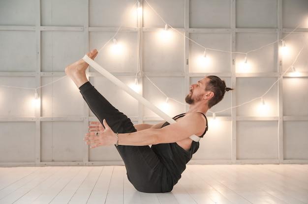 Um homem pratica ioga em um estúdio brilhante. asanas de homem e ioga com elástico. Foto Premium