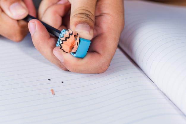 Um homem que aponta o lápis na página de livro de papel de linhas brancas Foto Premium