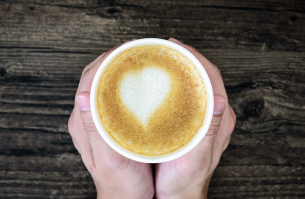 Um homem que guarda o café do latte com o leite do coração da arte isolado na tabela de madeira marrom. apartamento colocar com uma xícara de café dos namorados conceito. Foto Premium