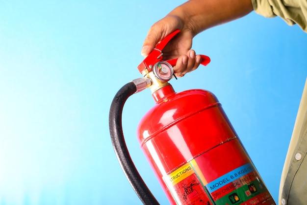 Um homem que guarda o extintor de incêndio no fundo azul. Foto Premium