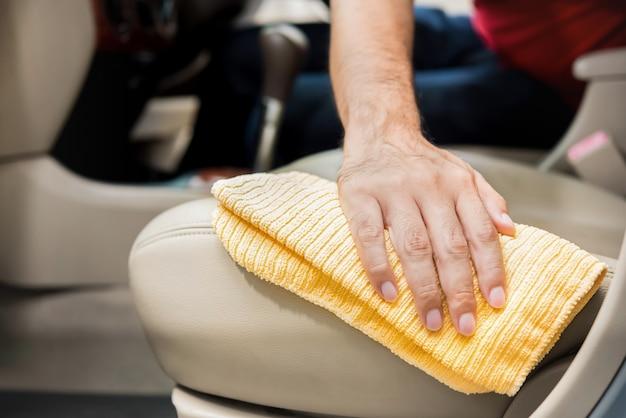 Um homem que limpa o assento de carro de couro bege com pano de microfibra Foto Premium