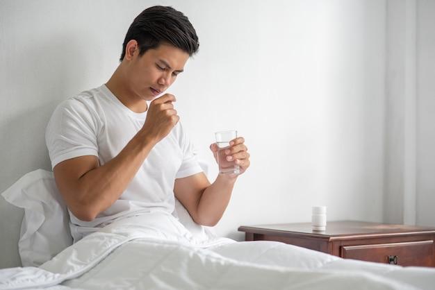 Um homem que não está bem no sofá e está prestes a tomar antibióticos. Foto gratuita