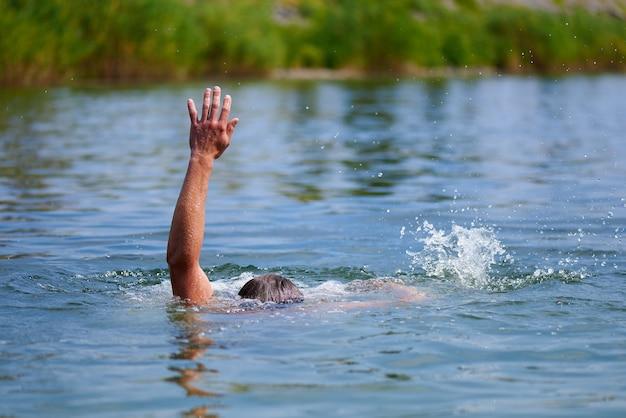 Um homem se afogando em uma lagoa. acidentes na água. Foto Premium