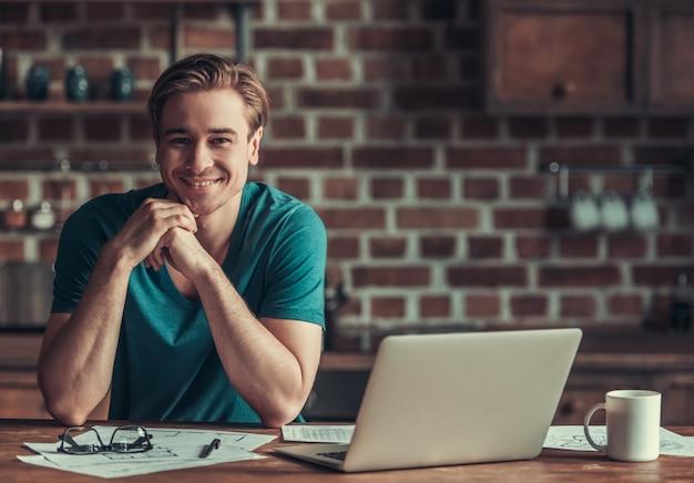 Um homem se senta à mesa e trabalha no laptop. Foto Premium