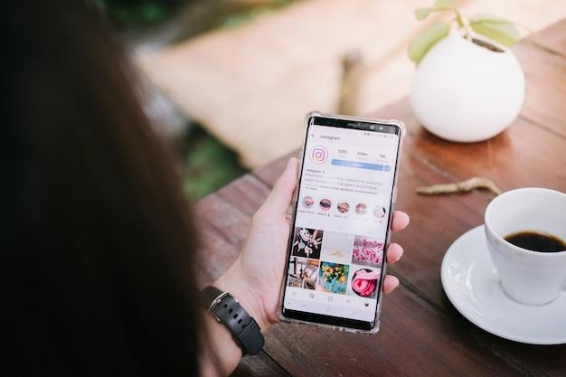 Um homem segura samsung nota 8 com aplicativo instagram na tela. Foto Premium