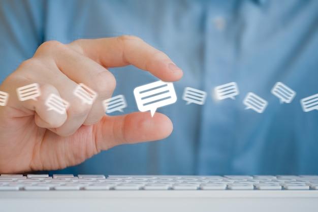 Um homem segura um ícone de mensagem com os dedos. o processamento de recursos e revisões. Foto Premium